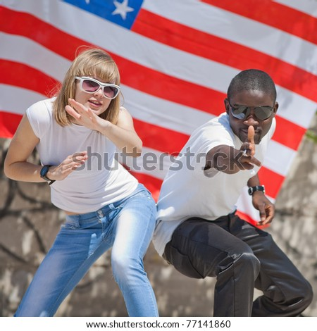 White girl and black guy dancing outdoors. White girl and black guy on background of American flag - stock photo