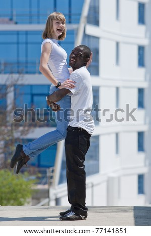 White girl and black guy outdoors. Young man and woman dancing against hotel - stock photo