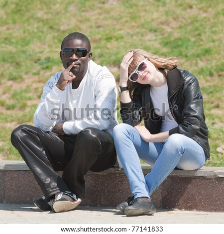 White girl and black guy outdoors. Young man and woman sitting in the park - stock photo