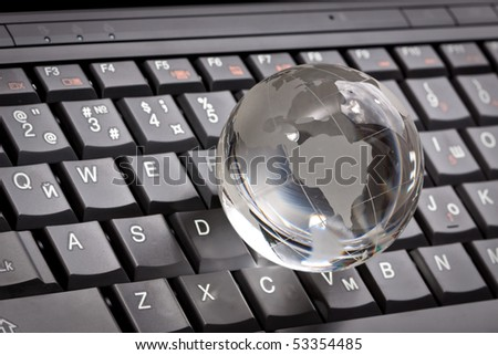 white glass globe on a laptop keyboard
