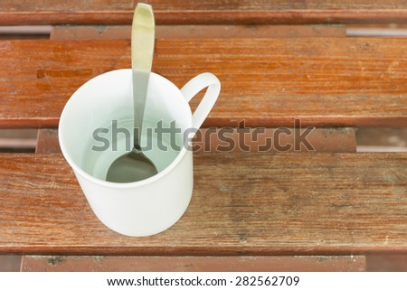 White glass of water and a spoon inside. On wood background - stock photo