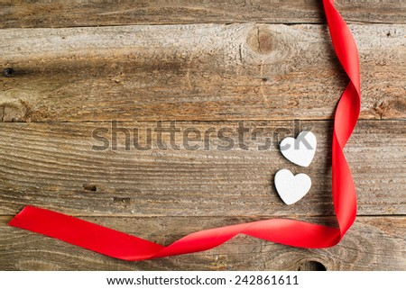 White glitter hearts with red satin ribbon on reclaimed wood, valentines day background. - stock photo