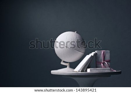 white globe and white books on white round table on dark background