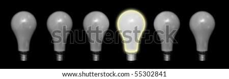 White glossy light bulb isolated on black background next to dull ones. A bright idea concept. - stock photo