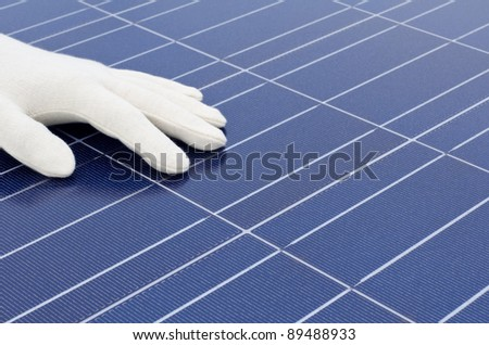 White gloved hand in front of solar cells - stock photo