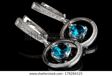 White gold earrings with topazes, isolated on black background - stock photo