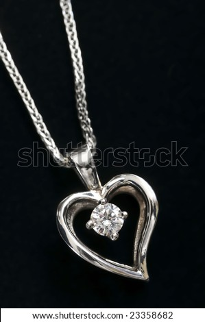 White gold heart pendant with diamond on a chain - stock photo