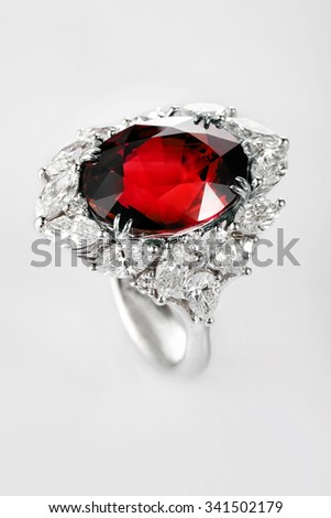White gold or silver ring with diamonds and red ruby gemstone on gray background. Selective focus - stock photo