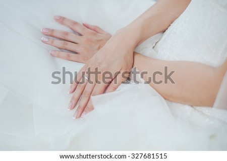 White gold ring with diamonds on the hand of the bride. Bride in white dress. - stock photo