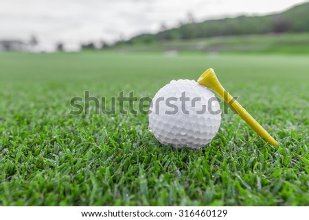White golf ball and a single yellow tee - stock photo
