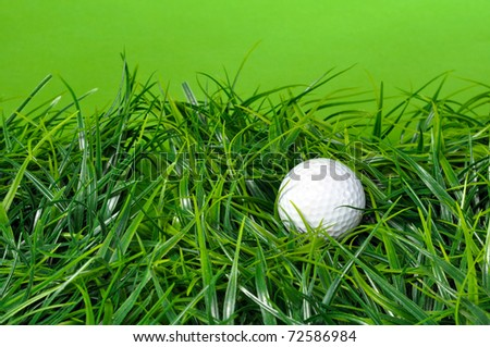 White golf ball laying in grass with green background and copy space - stock photo