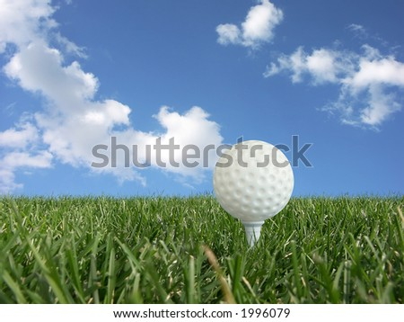 White golf ball on a tee in grass over blue sky - low perspective - stock photo