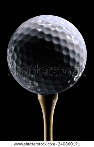White Golf Ball on a Wooden Tee with dramatic lighting - stock photo