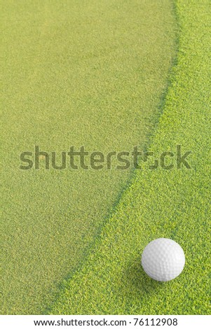 white Golf ball on green grass left side background ,in the hole.copy Space for tex
