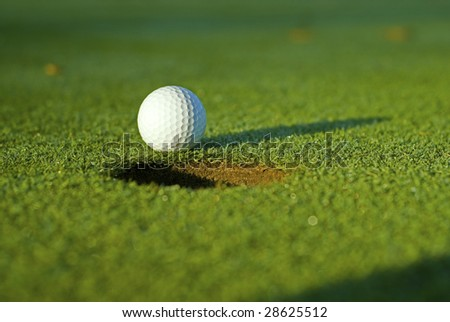 White golf ball on putting green next to hole with long shadow and selective focus on ball.