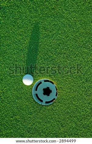 White golf ball on putting green next to hole with long shadow - from top down. - stock photo