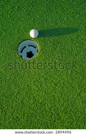 White golf ball on putting green next to hole with long shadow - from top side down. - stock photo