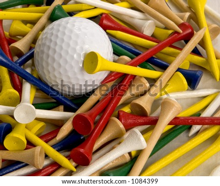 White golf ball surrounded by different color tees. - stock photo