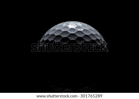 White golf ball with hexagonal dimples fading into a black background - stock photo