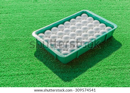 White golf balls contrasting with green grass background. - stock photo