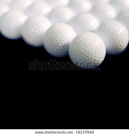 White golf balls on black square background with shallow dof - stock photo
