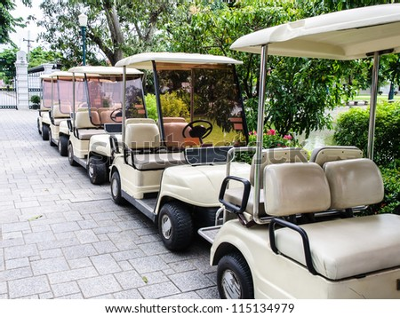 White golf cart is park near the entrance of palace.