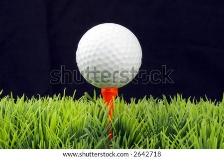 white golfball in orange tee, green fairway, isolated on black background - stock photo