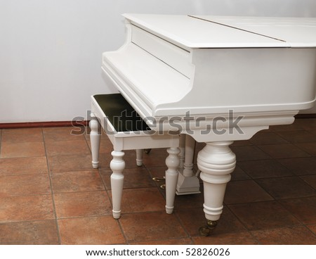 white grand piano and bench in a room - stock photo