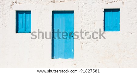White greek house with blue door and two blu windows - stock photo