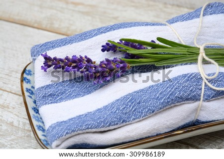 white grey old white wooden shelves background with empty copy space and lavender flowers on a saucer plate blue napkin towel decoration - stock photo