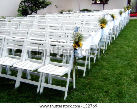 White Guest Chairs Assembled at an Upscale Outdoor Wedding - stock photo