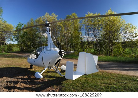 White gyroplane parked on the private airfield in the sunny day