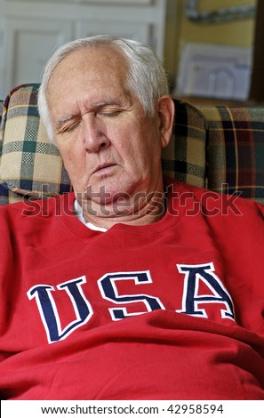 White-haired Senior man in bright red sweat shirt enjoys his retirement as he sleeps in his easy chair. - stock photo