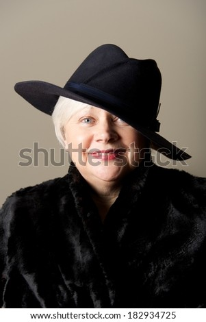 White-haired woman in black hat and coat