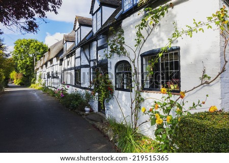 white half timbered house in an english village - stock photo