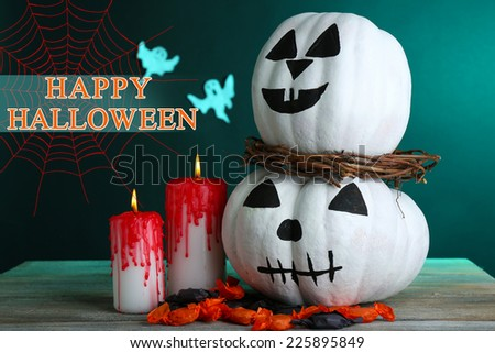 White Halloween pumpkins and candles on wooden table on dark green background - stock photo