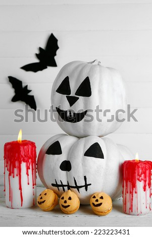 White Halloween pumpkins, candles and candies, on color wooden background - stock photo