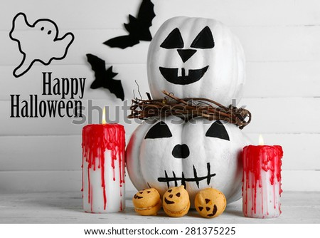 White Halloween pumpkins, candles and candies, on white wooden background