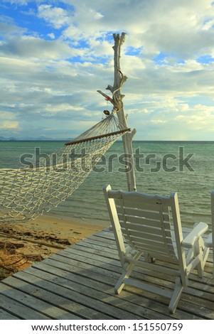 White hammock and wooden beach chair over sea at dusk - stock photo