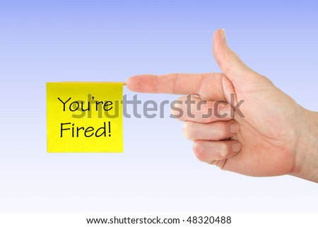 White hand pointing finger with a yellow you're fired note attached - stock photo