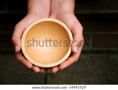 White hands holding a wooden begging bowl - stock photo