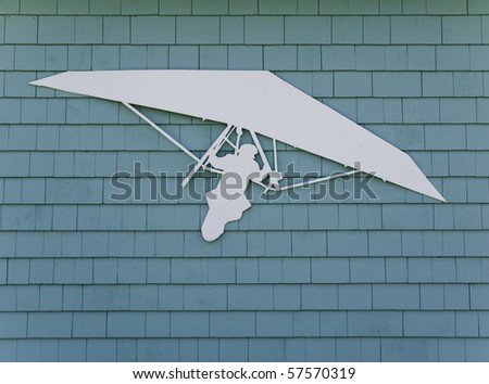White hang gliding symbol attached to a greenish blue wooden structure