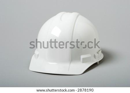 White hardhat on grey background - stock photo