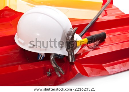 White hardhat, red and yellow acrylic coated roof, hammer and crowbar with screw - stock photo