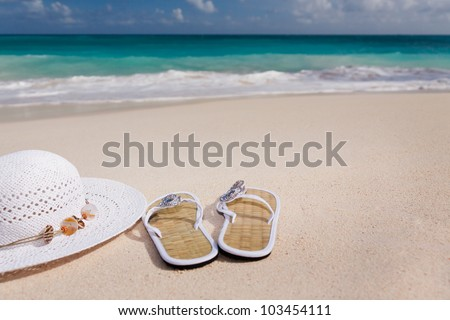 white hat and flip-flops on the beach with blue sea in the background - stock photo
