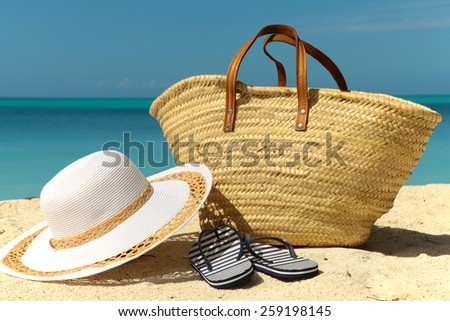 white hat and wicker bag with stripey flip flops on the beach