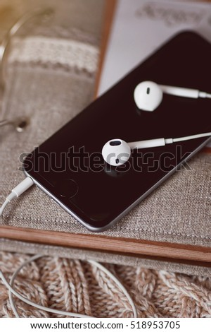 White headphones with old book and black smartphone.