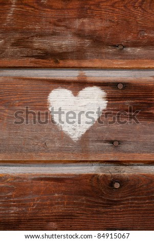 White heart as a symbol of love made with chalk on a brown wooden wall - stock photo
