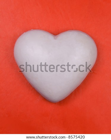White heart (ginger cake) on red background. - stock photo