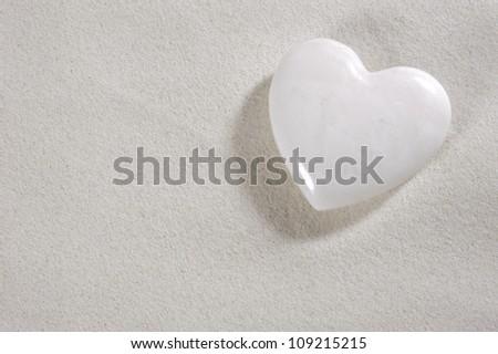 white heart in white sand - stock photo